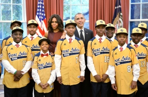 President Barack Obama and first lady Michelle Obama meet with the Jackie Robinson West All Stars in the Oval Office of the White House, November 6, 2014 in Washington, DC. The team won the United States championship before having its title stripped only a few short months later. (Photo by Olivier Douliery-Pool/Getty Images)